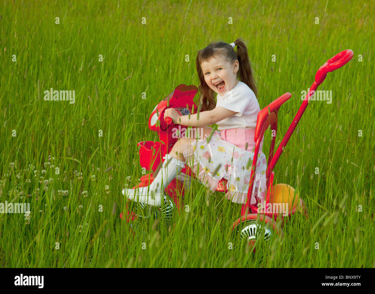 The cheerful little girl goes on a bicycle on a grass Stock Photo