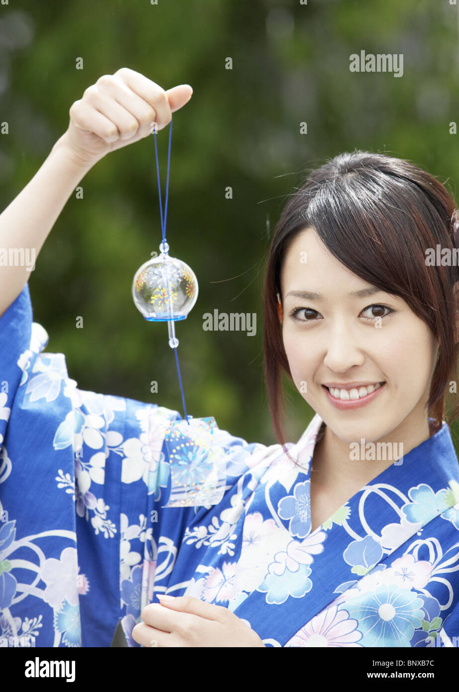Young woman holding wind chime - Stock Image