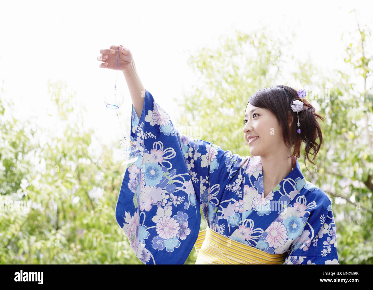 Young woman looking at wind chime - Stock Image