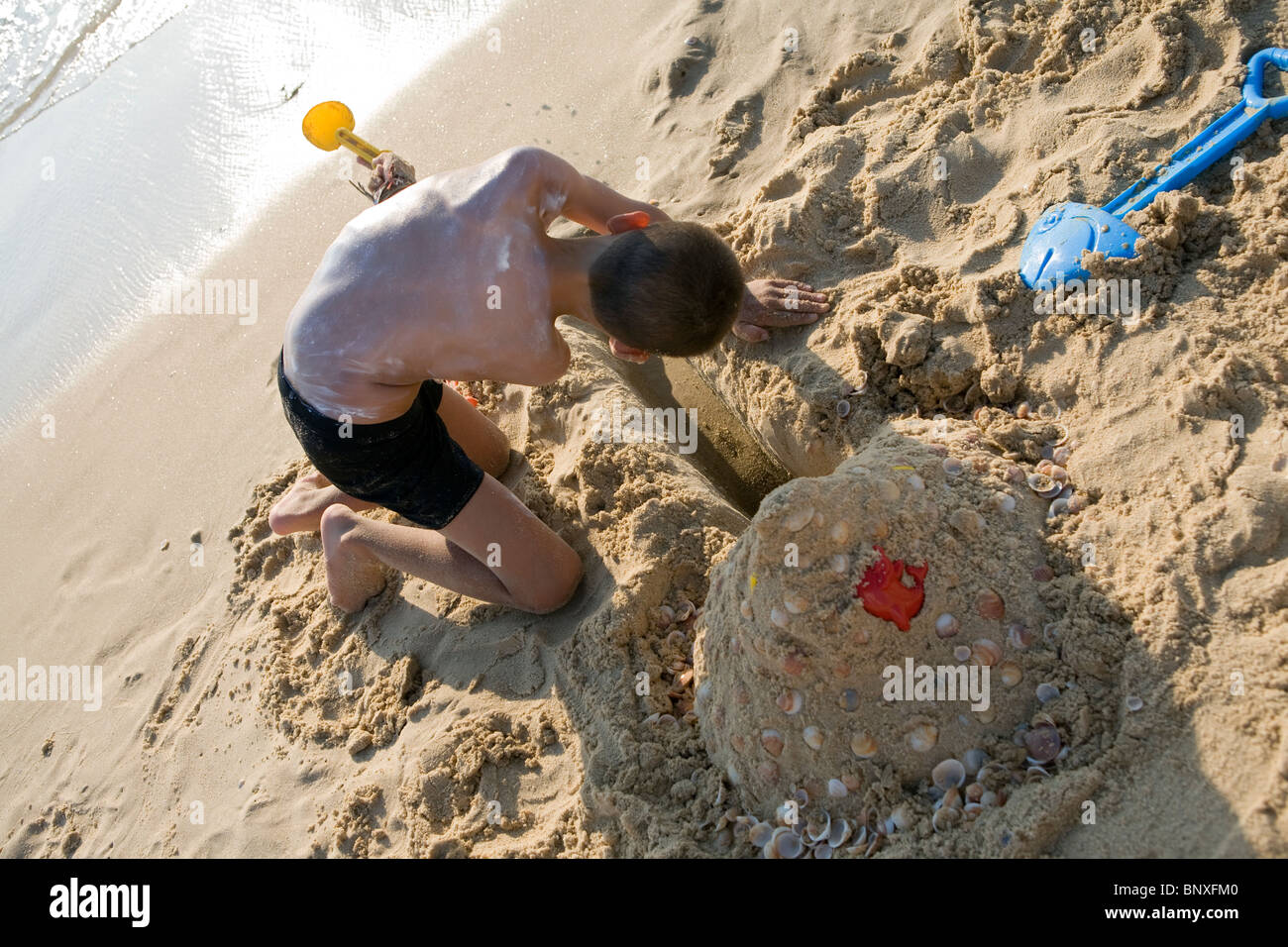 boy building sand castle by the sea on a sunny day - Stock Image