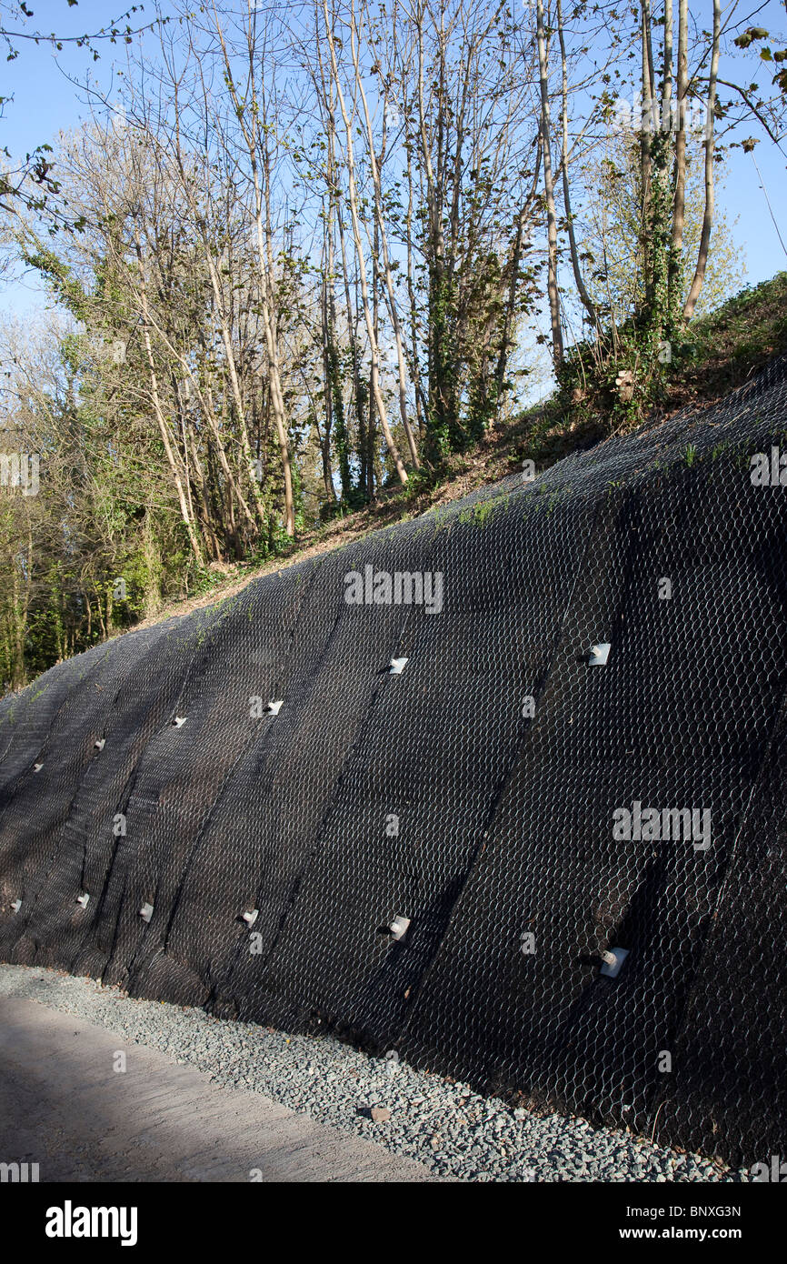 Unstable bank covered with retaining mesh and bolts to hold the bank in place Llansfeffan Wales UK - Stock Image