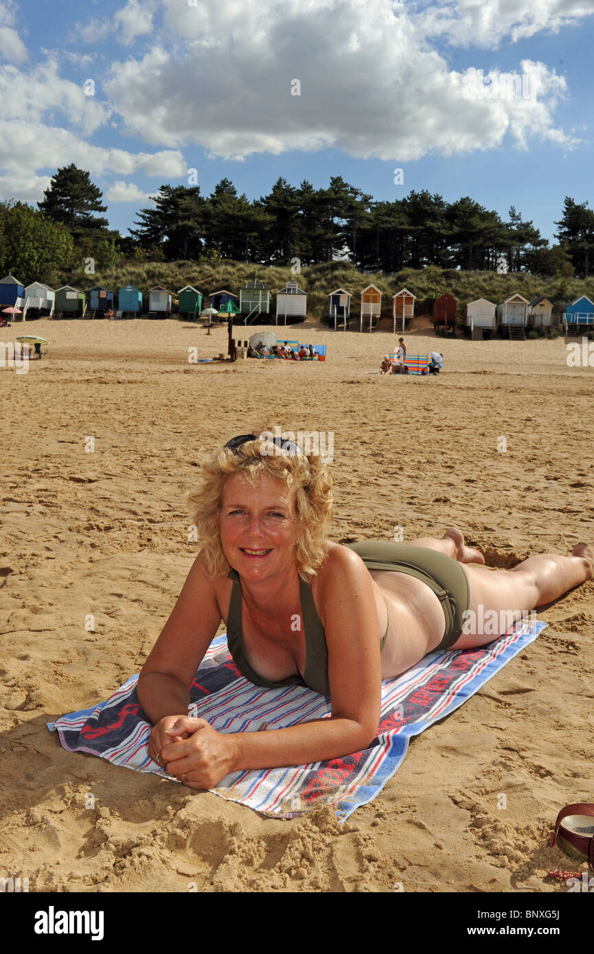 Middle aged woman sunbathing on beach at Wells next the ...