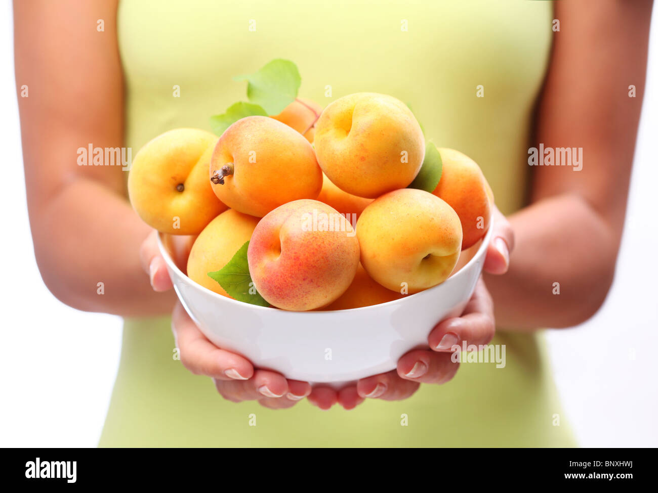 Crockery with ripe apricots in woman hands. - Stock Image