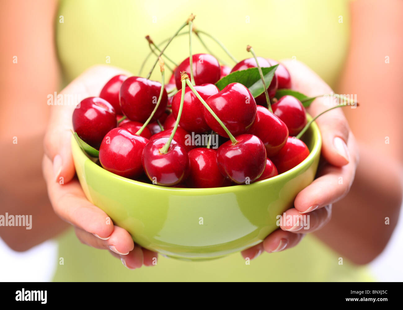 Crockery with cherries in woman hands. - Stock Image
