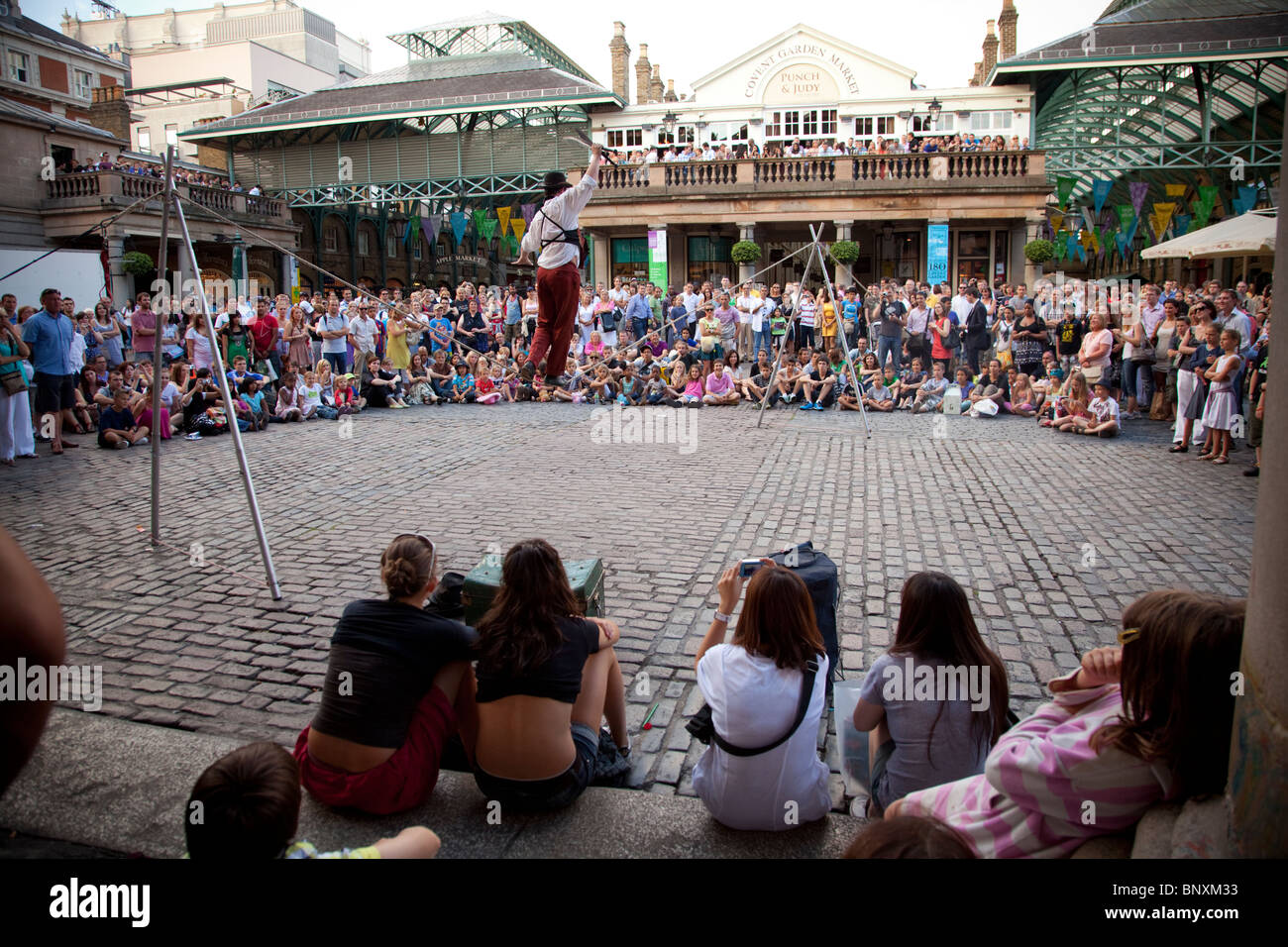Crowds watching the street performers at Covent Garden, London, England - Stock Image