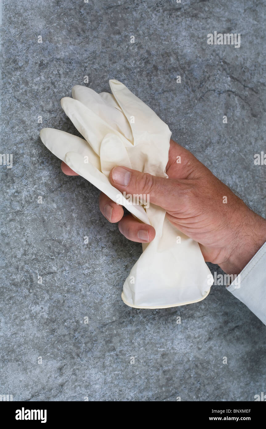 A male hand picking up a pair of medical latex rubber gloves - Stock Image