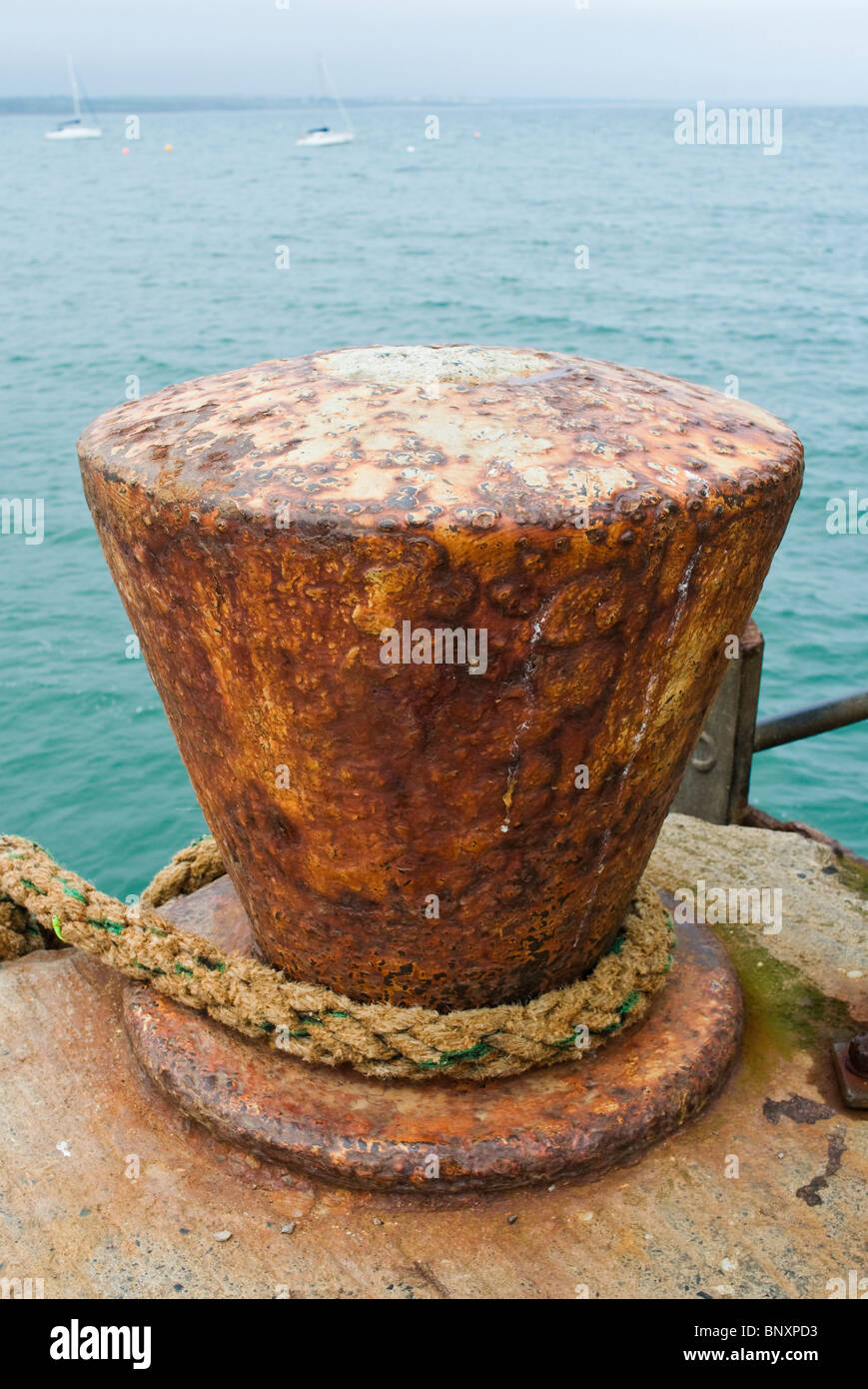 Rusty old cast iron bollard for mooring boats on the quay - Stock Image