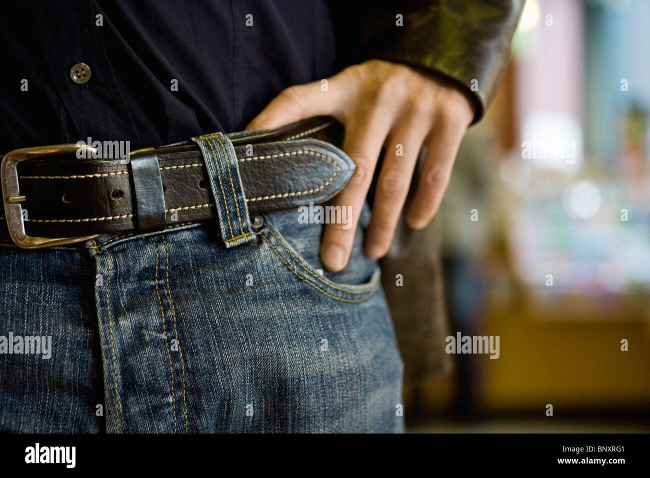 Person wearing jeans with belt, hand on hip, cropped - Stock Image