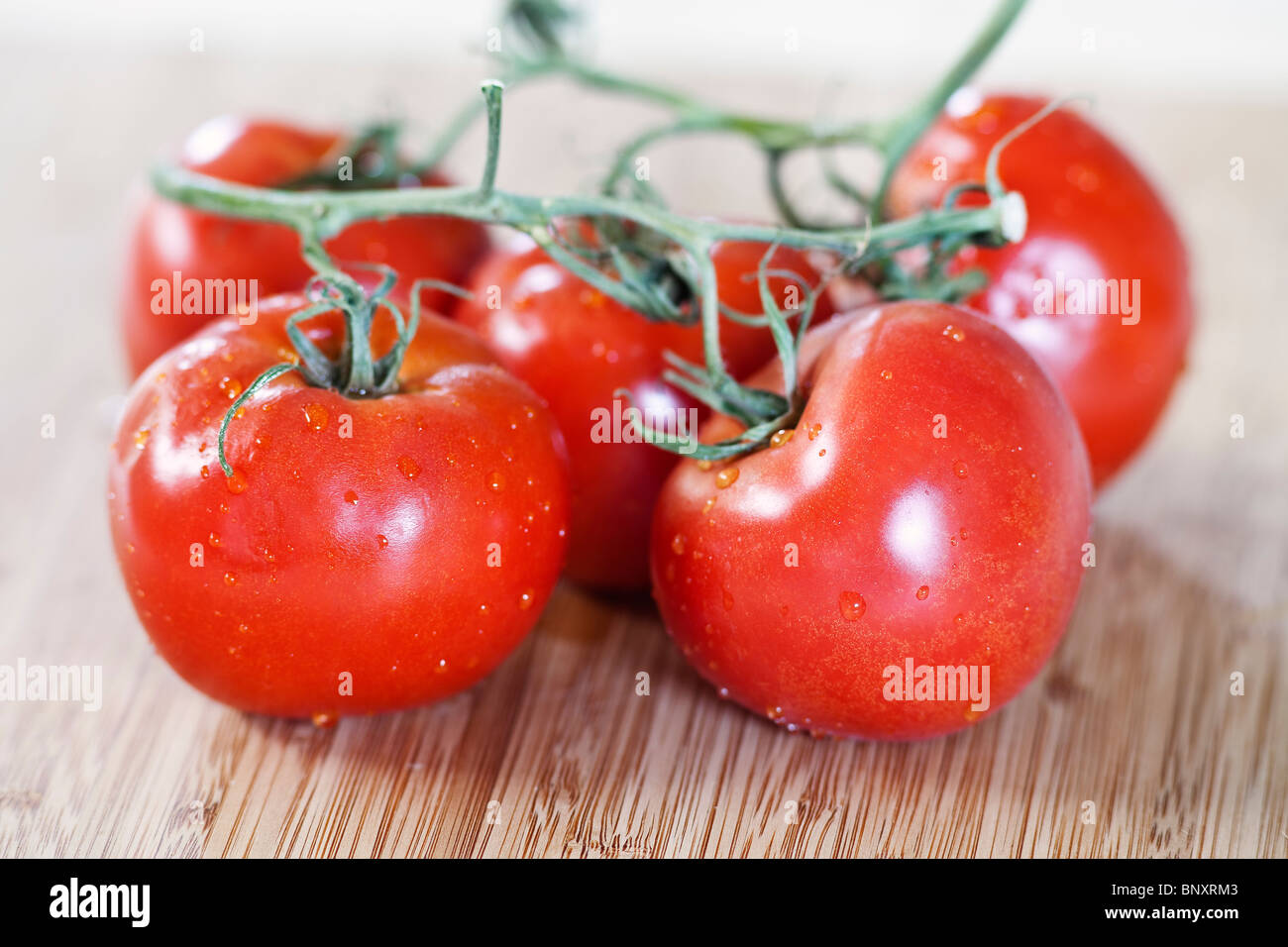 Vine ripened tomatoes on bamboo cutting board. - Stock Image