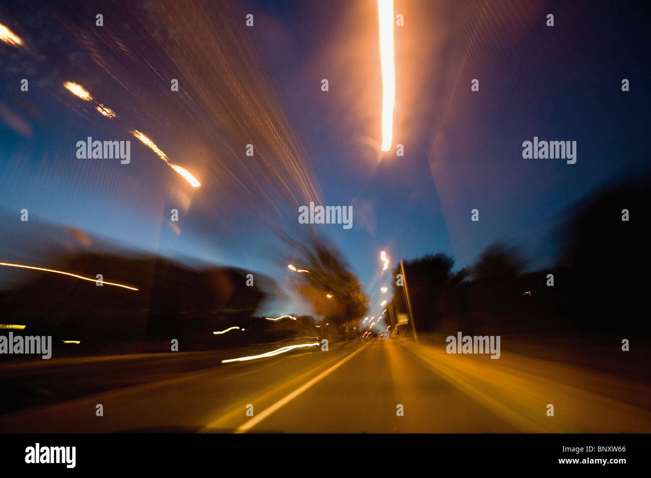 Light trails of traffic on busy street at night - Stock Image