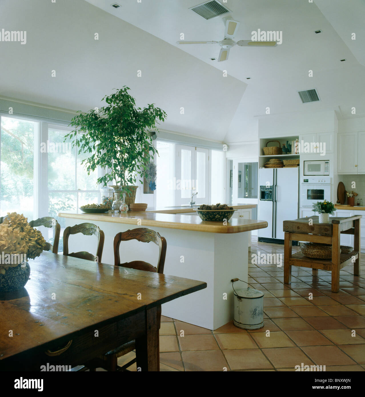 Old pine table and chairs in large modern open-plan kitchen dining ...