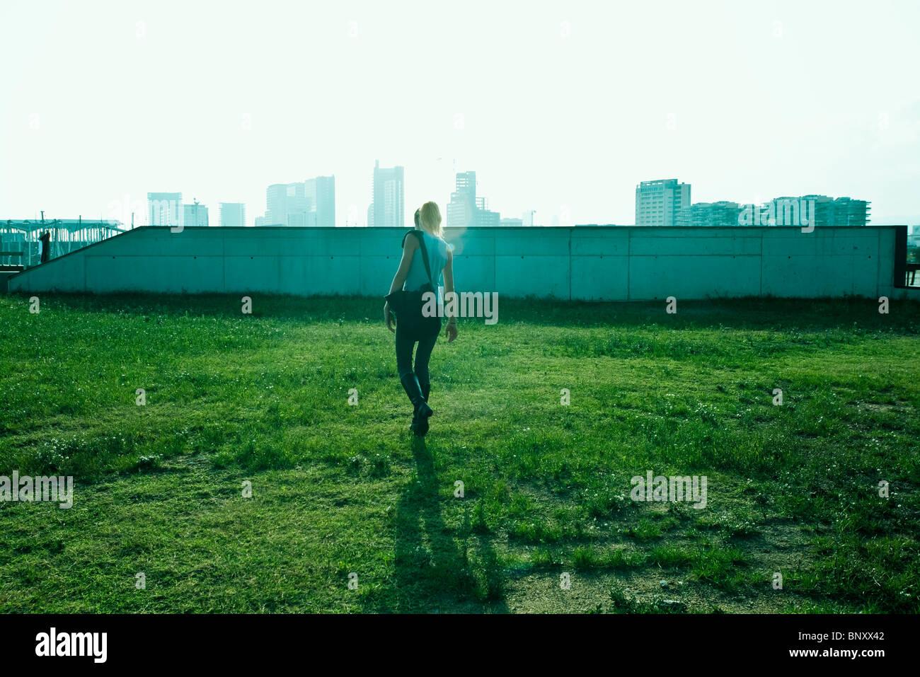 Teen girl walking across grass, urban skyline in background - Stock Image