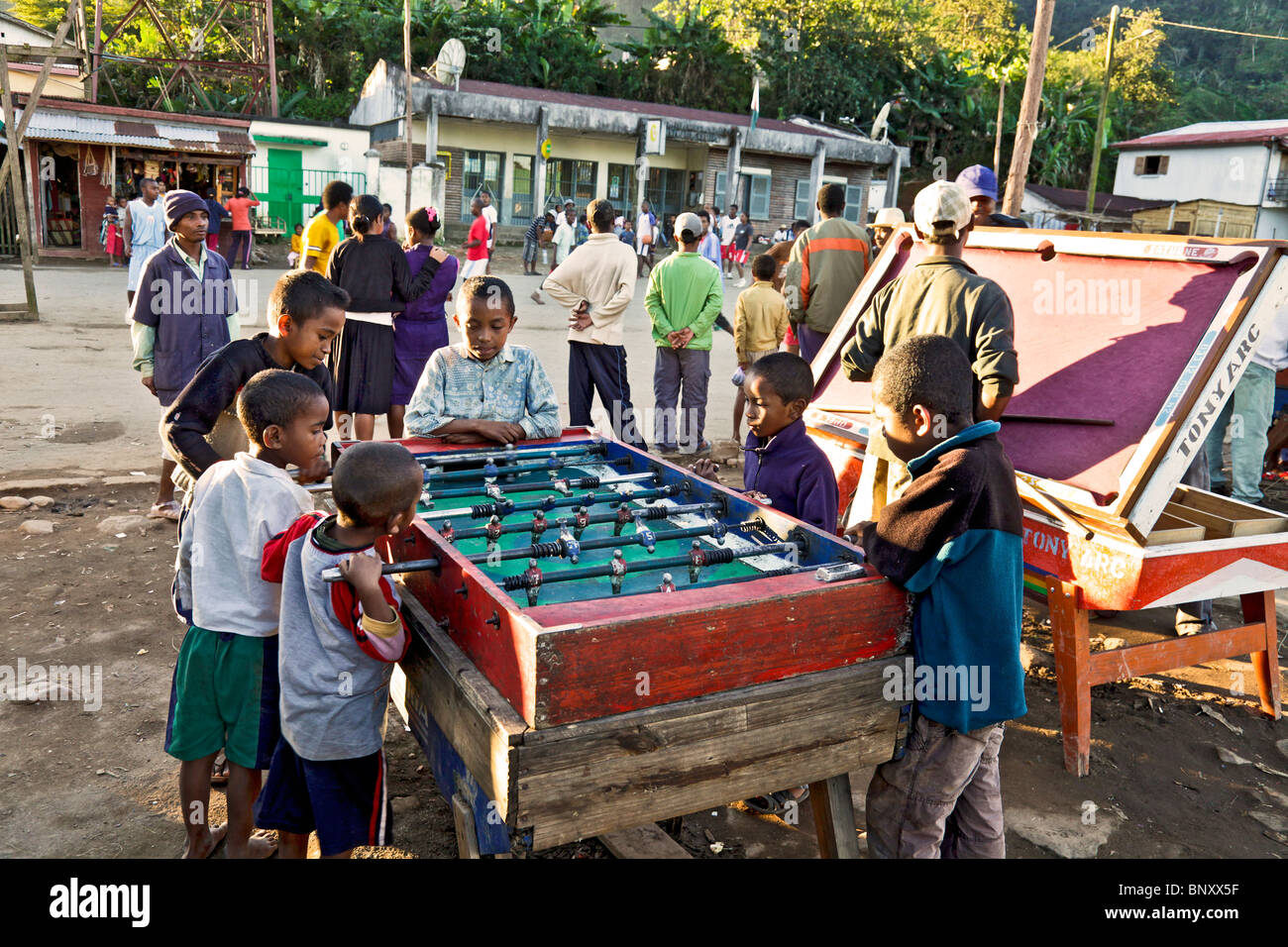 Boys playing table football/ Fussball / Fußball in Ranomafana village, Madagascar, while others watch a Basketball - Stock Image