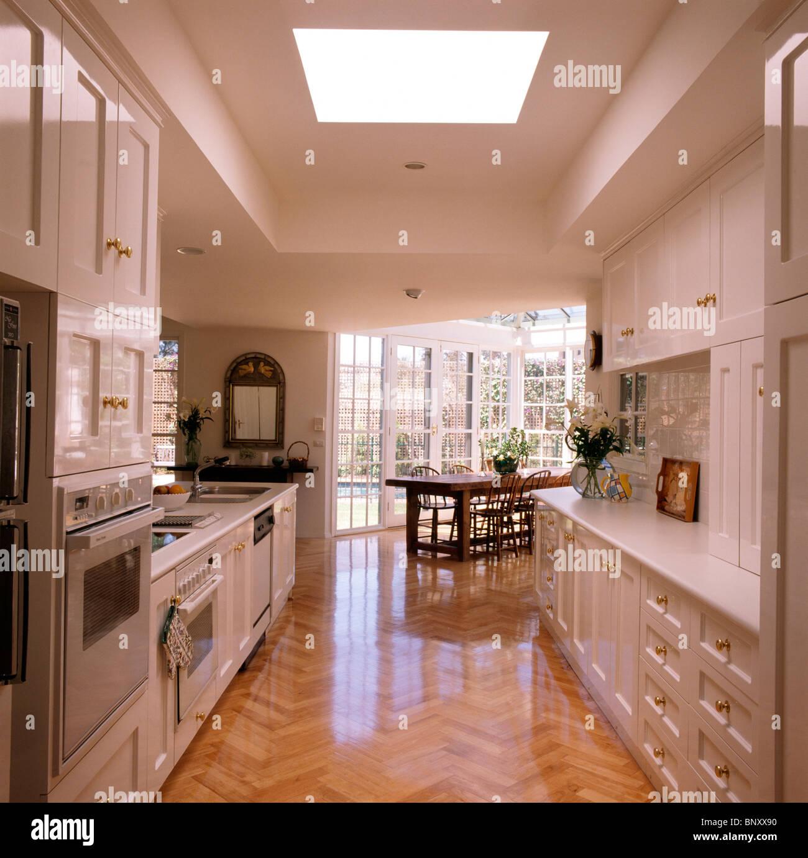 Polished wooden parquet flooring in modern open-plan white kitchen ...