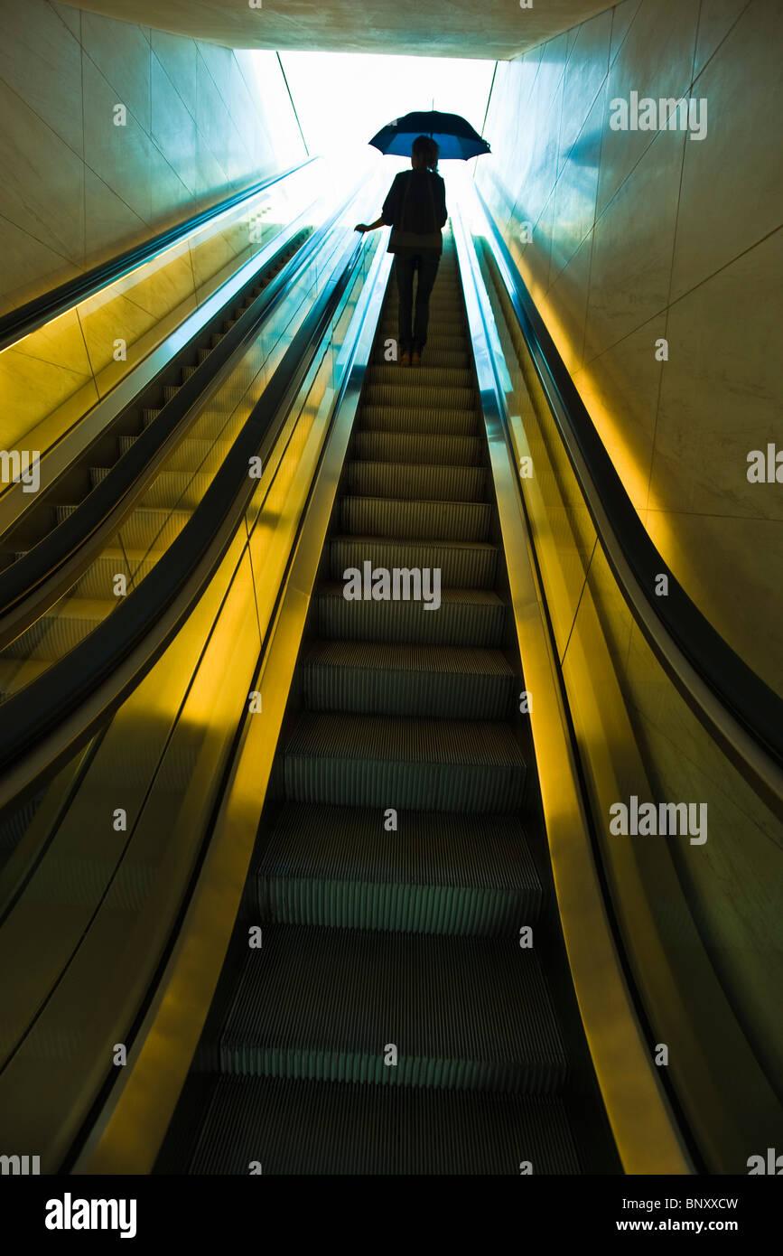Going up escalator holding open umbrella prepared to go outdoors - Stock Image