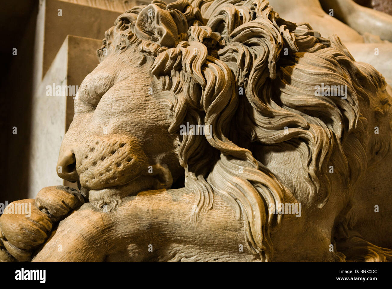 Statue of sleeping lion flanking Monument to Clement XIII, St. Peter's Basilica, Rome, Italy - Stock Image