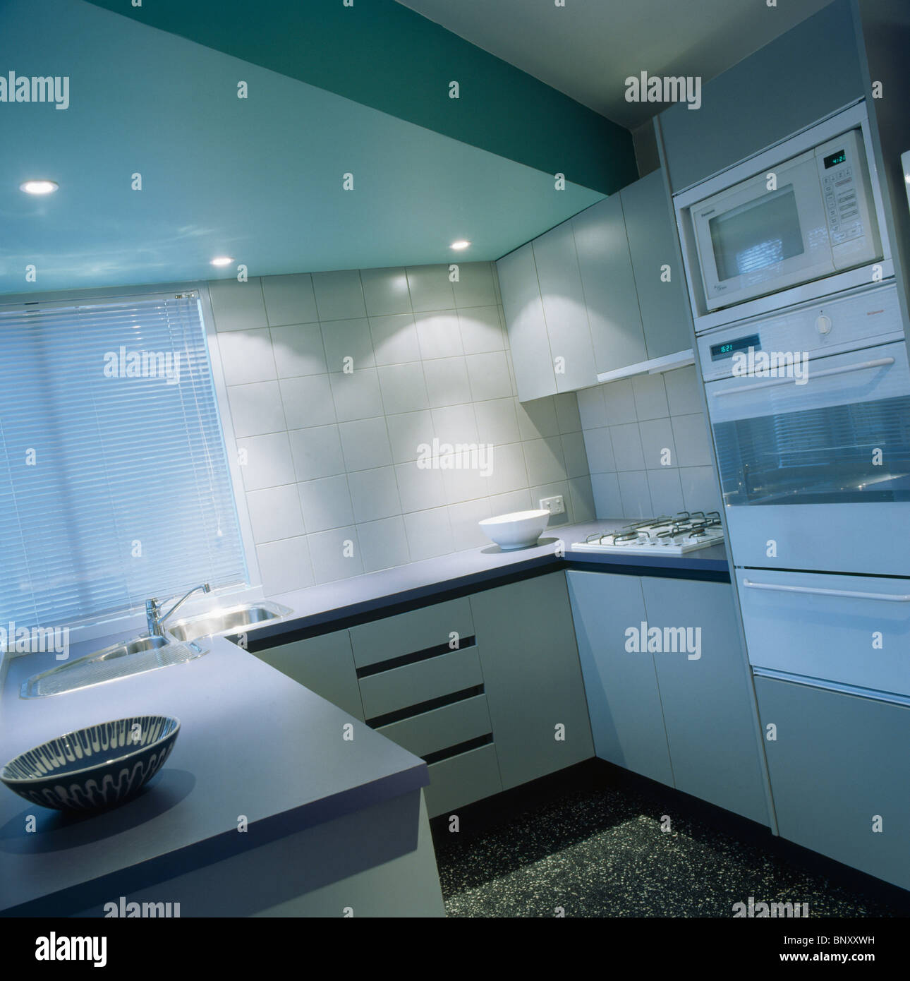 Recessed lighting and white tiled splash-back in modern pastel blue kitchen with wall-mounted double oven - Stock Image