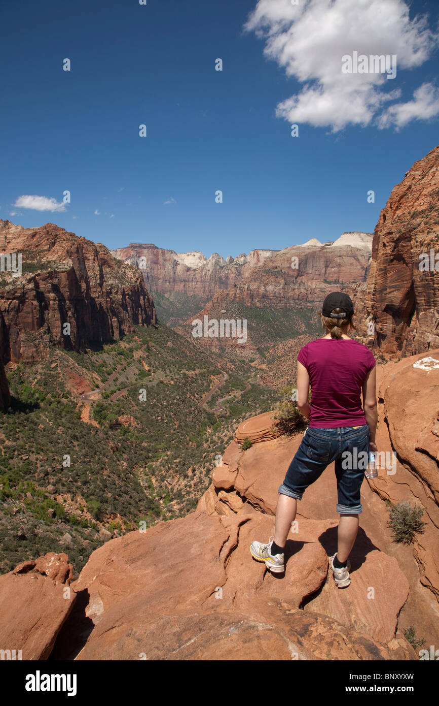 A tourist enjoys the view of lower Zion Canyon in Utah USA from the Overlook viewpoint on a sunny summer day - Stock Image
