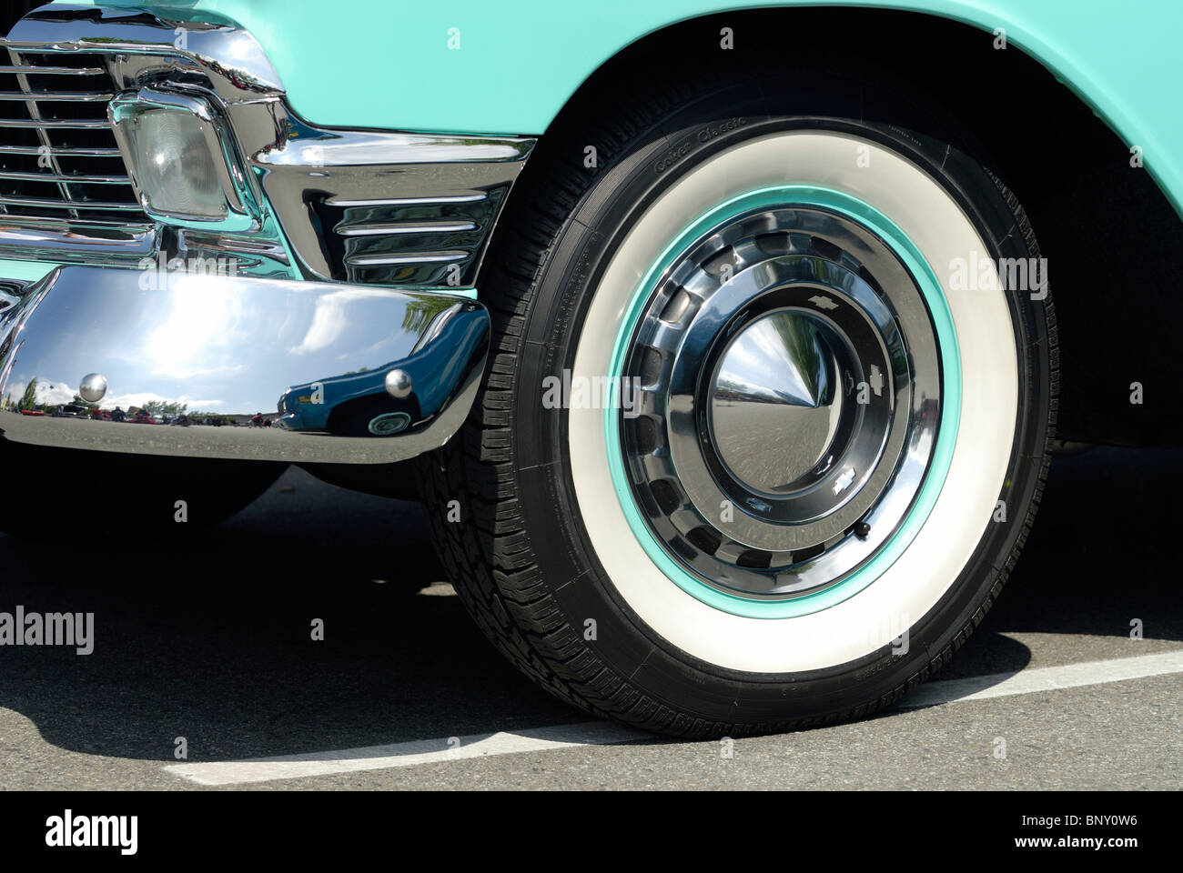 Side view of a classic 1959 Ford Sunliner Convertible automobile, showing part of its bumper and whitewall tire. - Stock Image