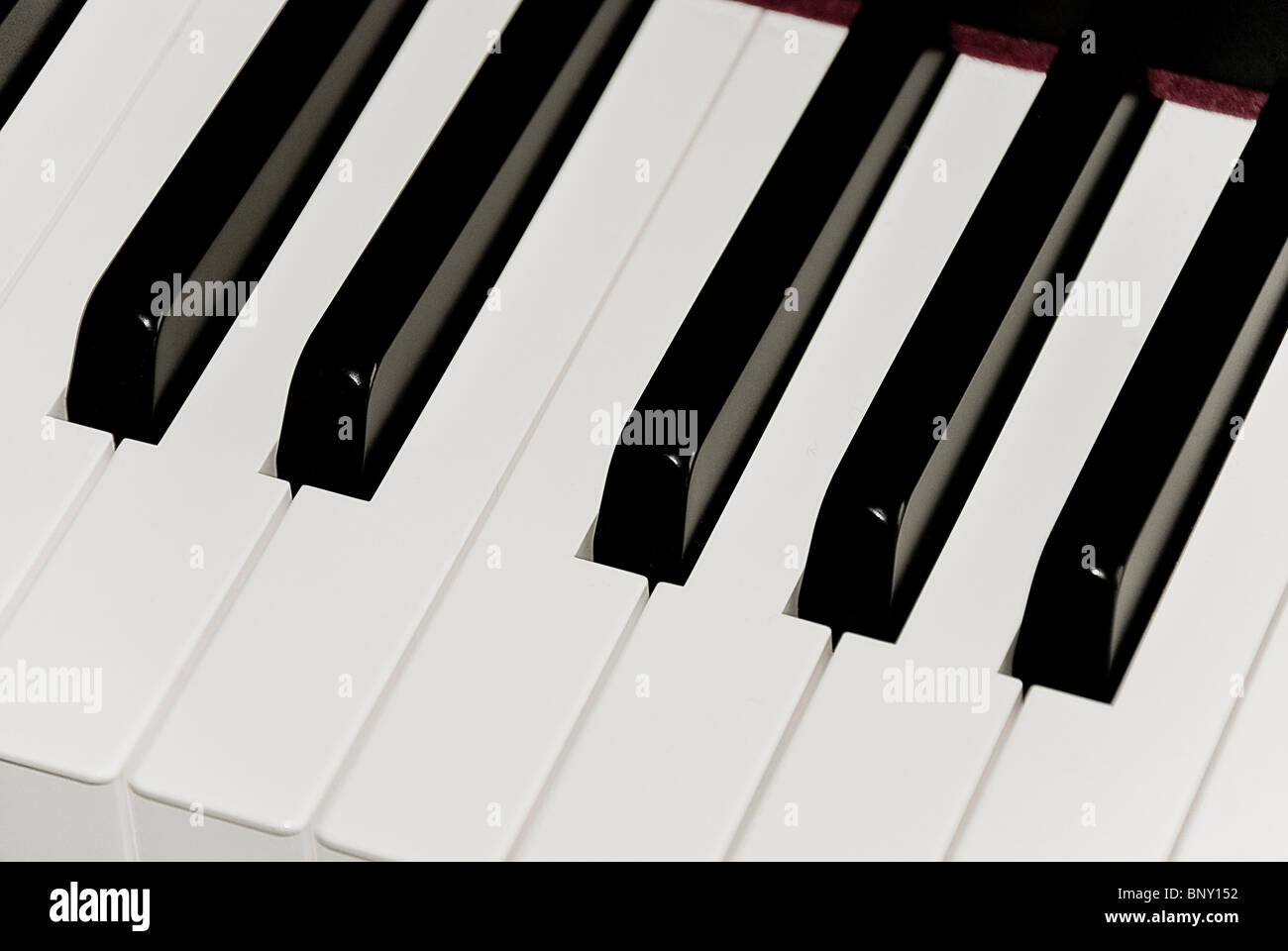 A closeup of black and white keys of piano keyboard featuring one octave key set. - Stock Image