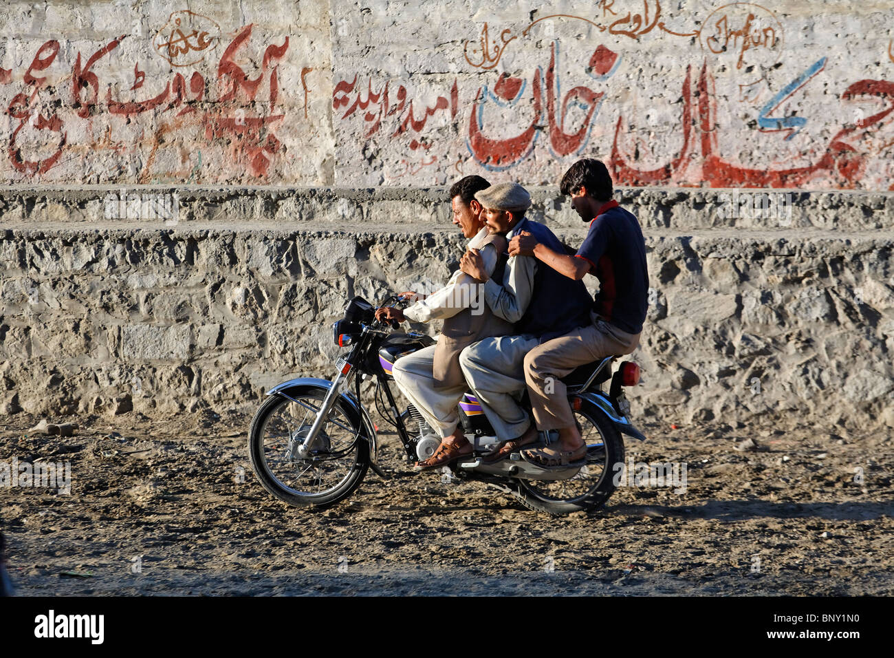 Pakistan - Gilgit - three men on a motorbike Stock Photo