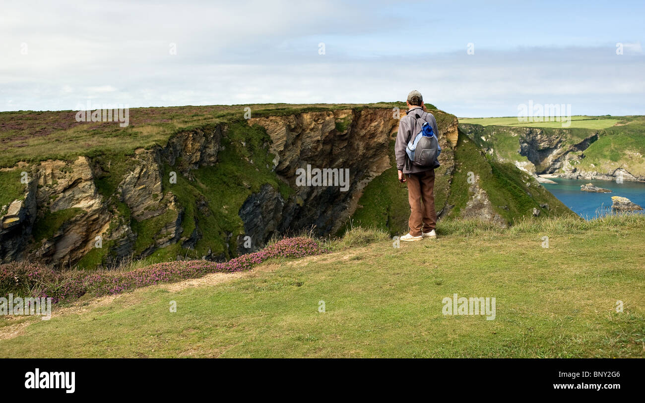 A walker standing on the cliff at Hells Mouth in Cornwall. - Stock Image
