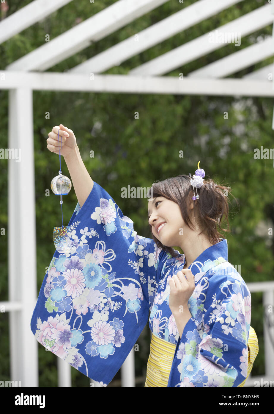 Young woman looking at wind chime Stock Photo
