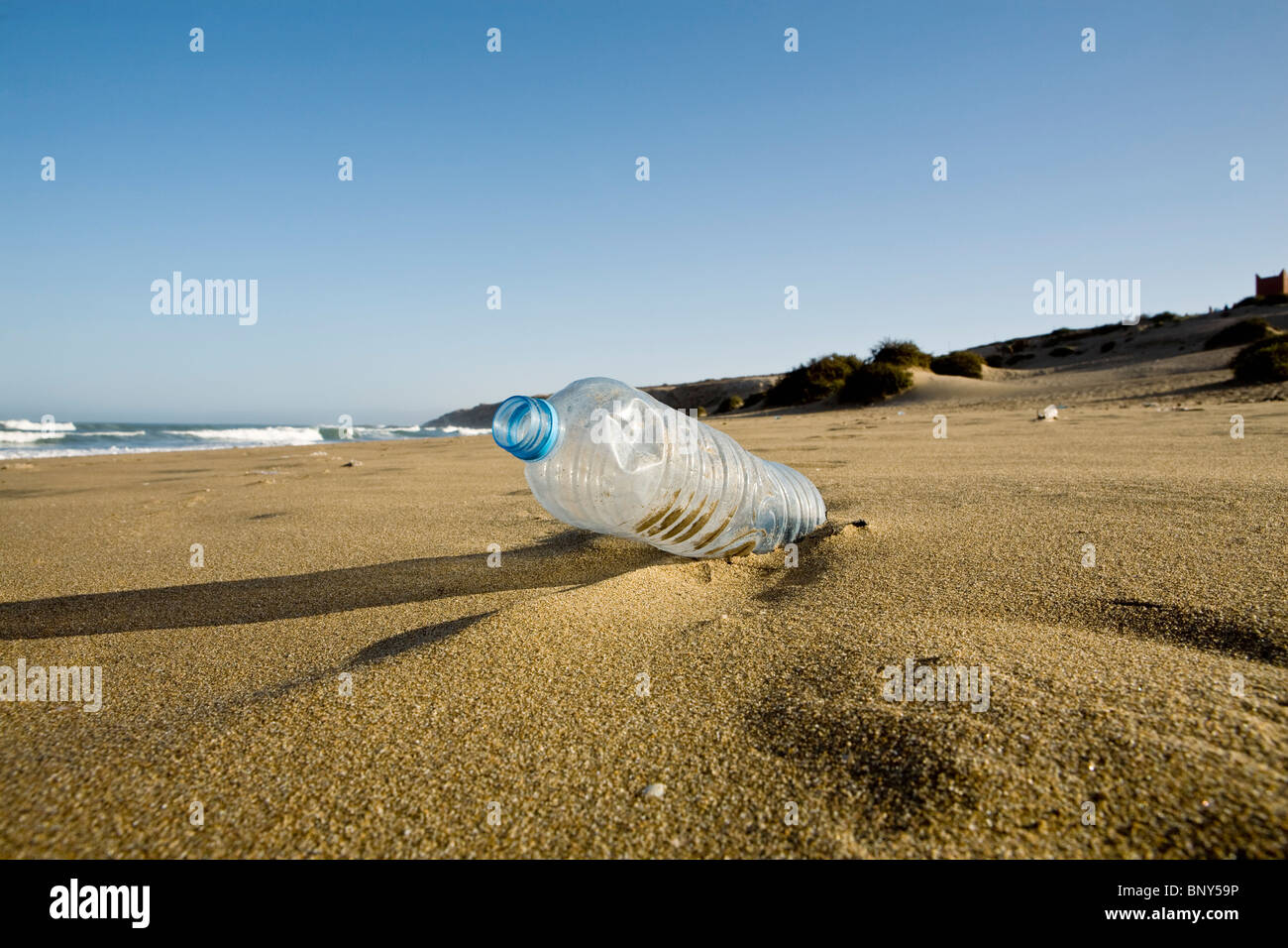 Plastic water bottle abandoned on beach, Souss-Massa National Park, Morocco - Stock Image