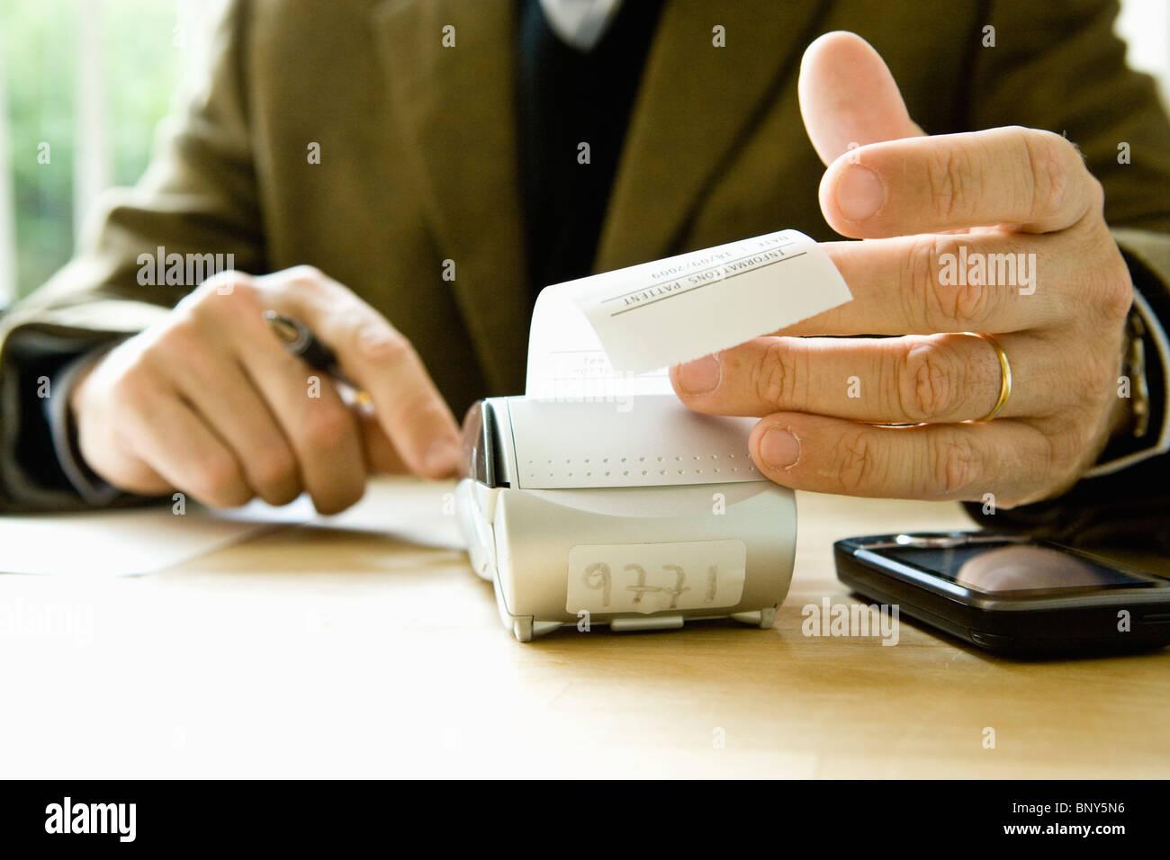 Calculating expenses using adding machine - Stock Image