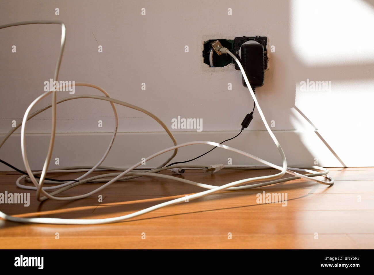 Electric cords plugged into exposed outlet - Stock Image
