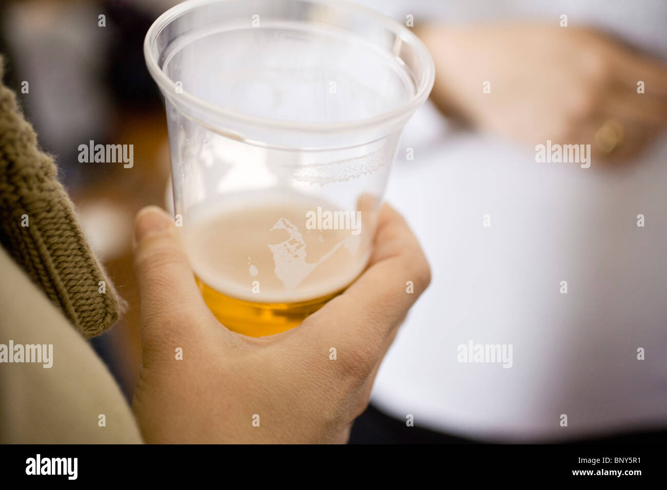 Person holding beer in plastic cup - Stock Image