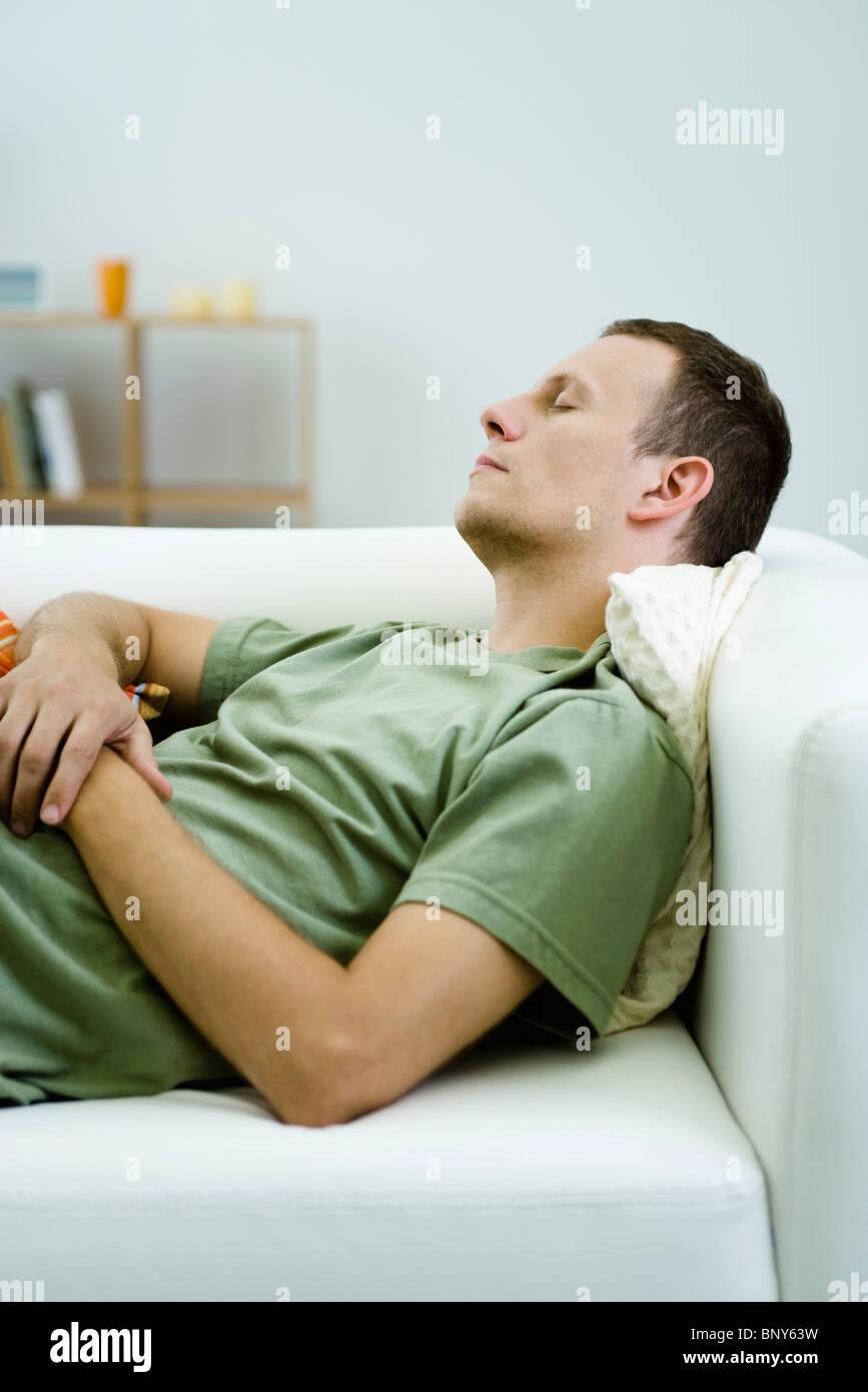 Man napping on sofa - Stock Image