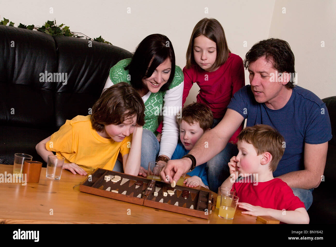 Big family is playing a boardgame in the livingroom - Stock Image