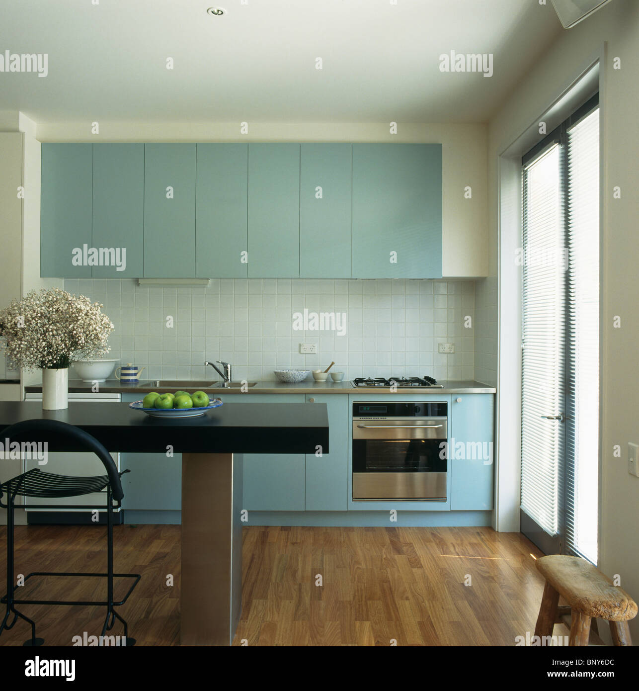 Pastel blue fitted units in modern white kitchen with black table