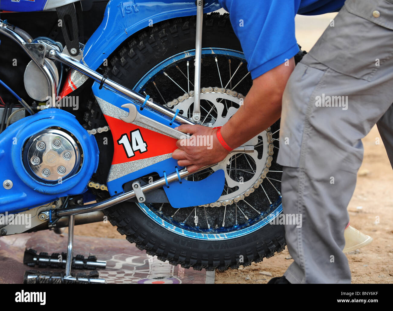 A speedway bike is worked on by a mechanic in the pits - Stock Image