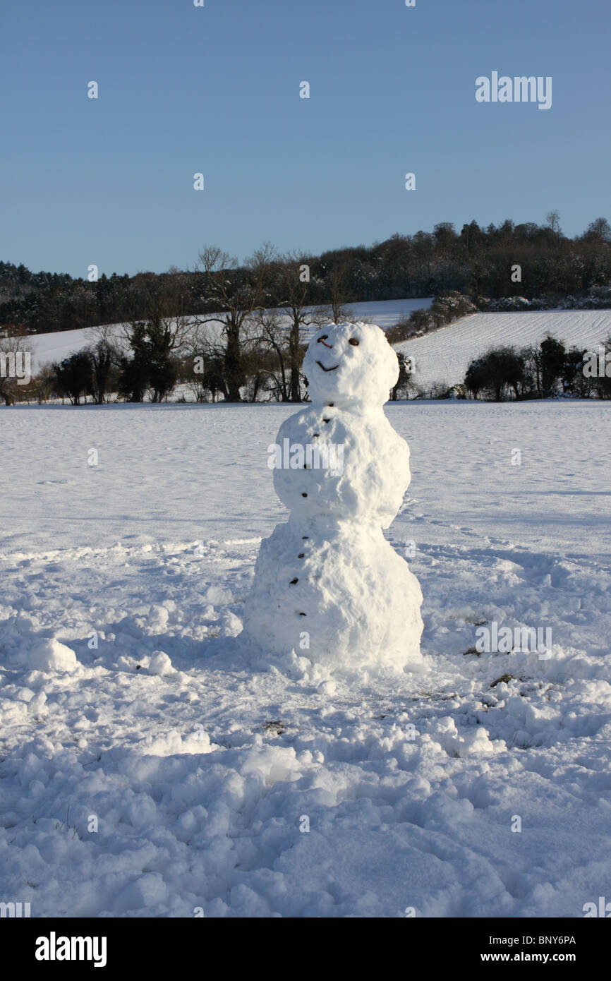 Snowman in field with Chiltern Hills behind at Mill End, Hambleden, Buckinghamshire, England, UK - Stock Image