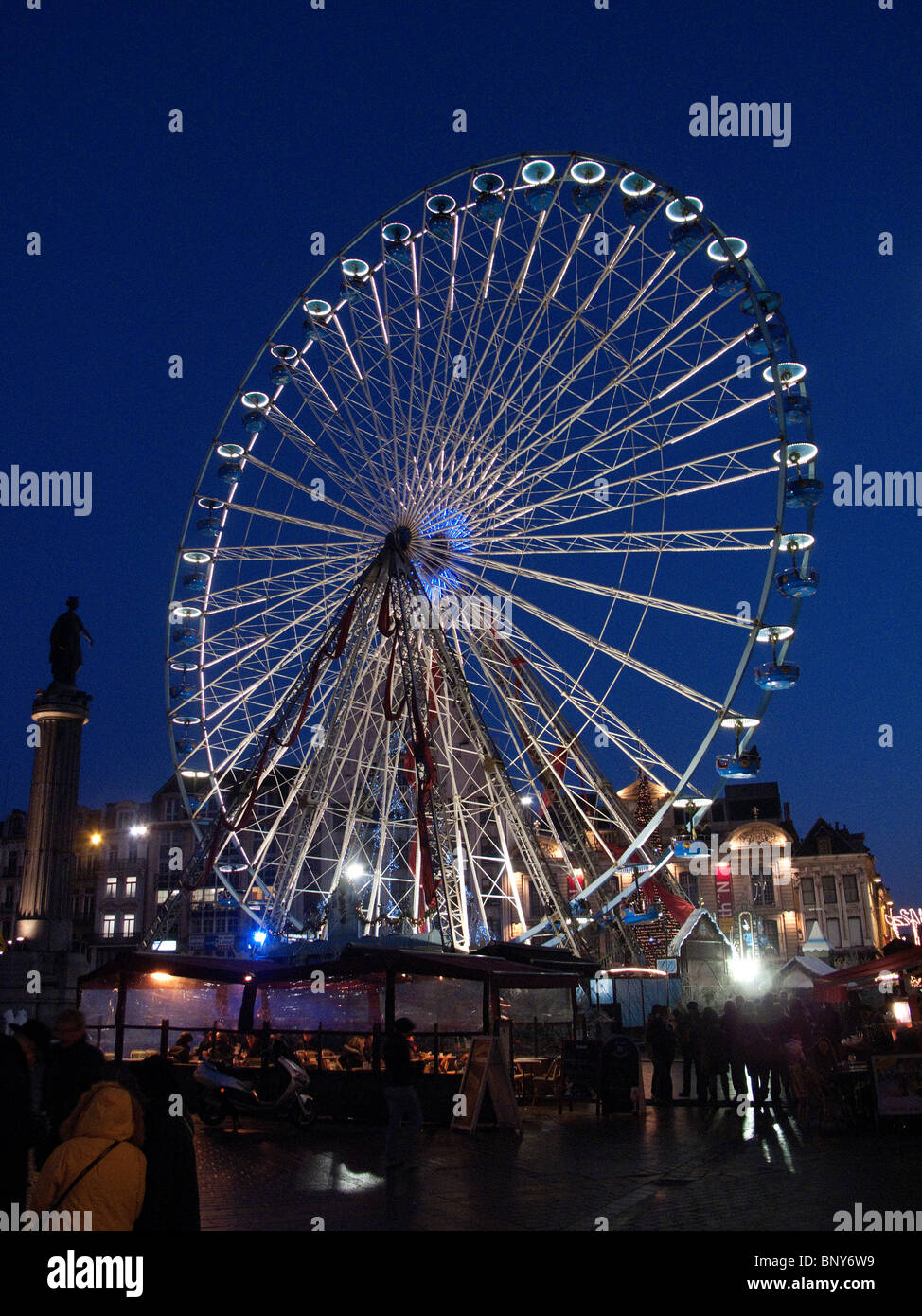 Ferris wheel in Grand Place, Lille, France, at dusk, during Christmas - Stock Image
