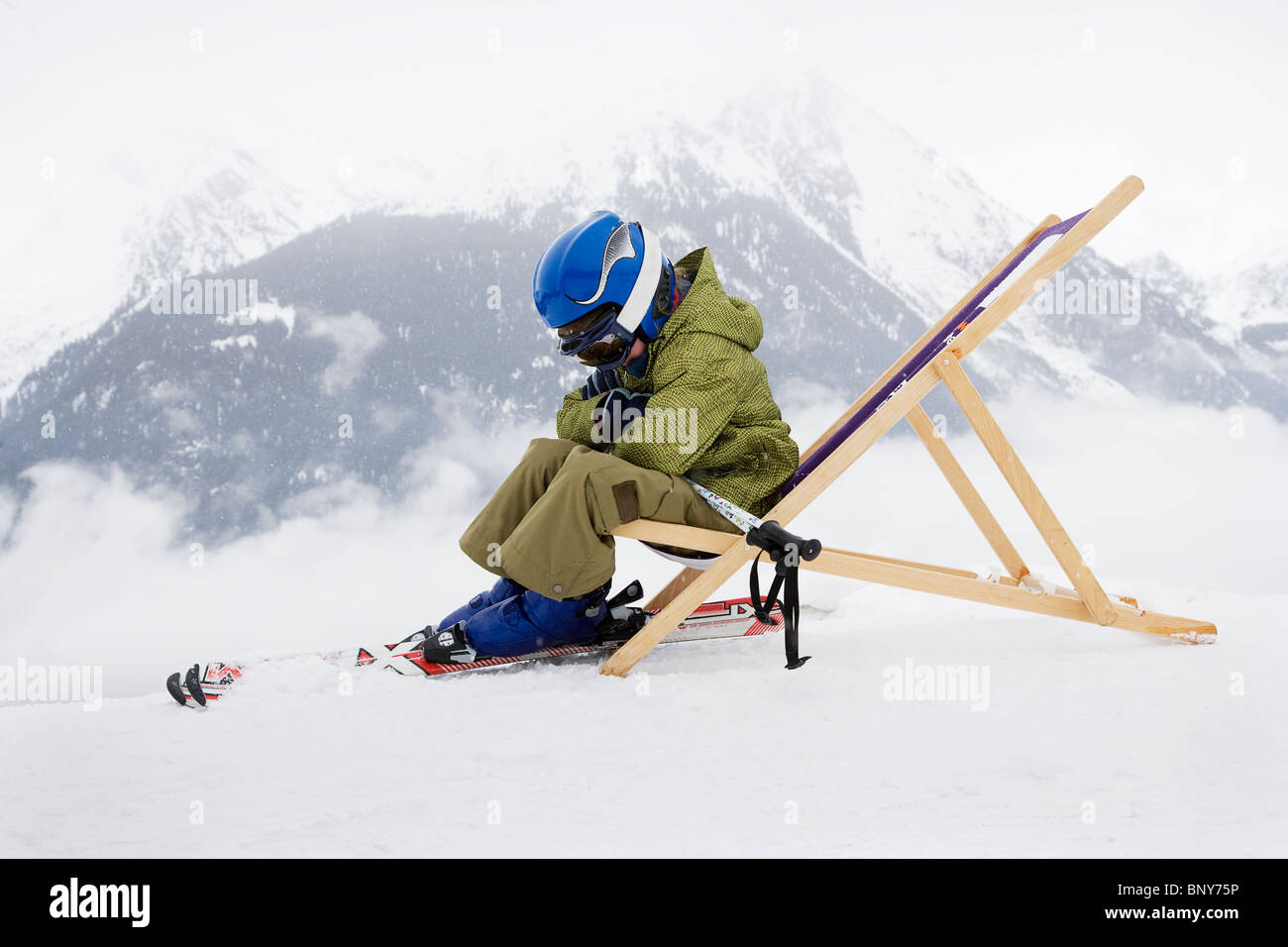 Child with skis sitting on deck chair - Stock Image