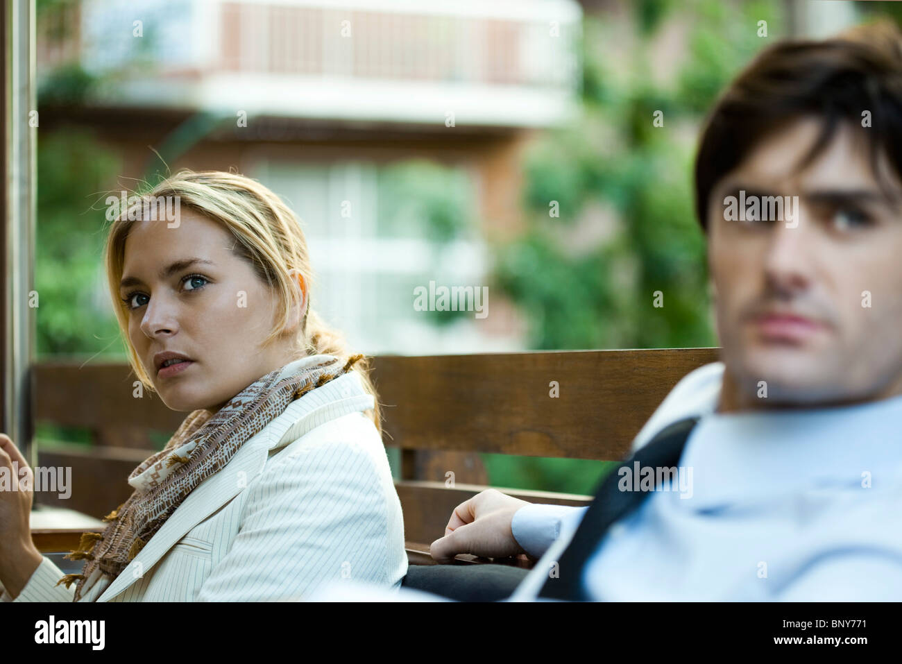 Couple sitting outdoors, woman looking away in distraction - Stock Image