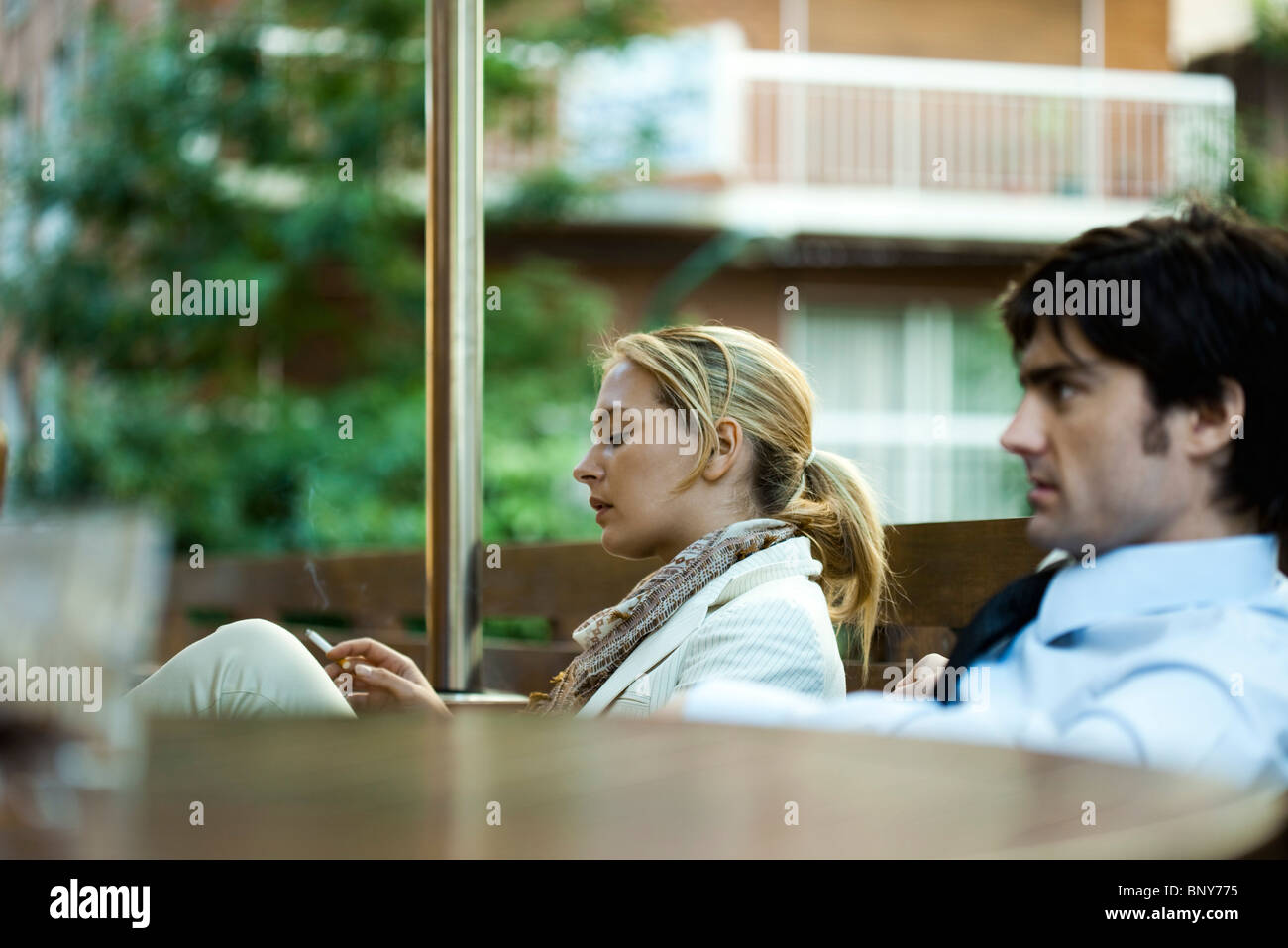 Unhappy couple sitting outdoors, woman smoking a cigarette - Stock Image