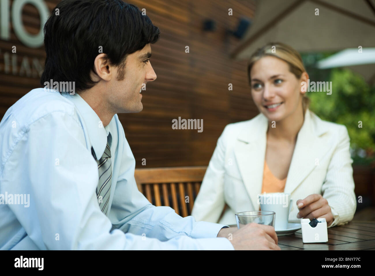 Couple relaxing together in outdoor cafe - Stock Image