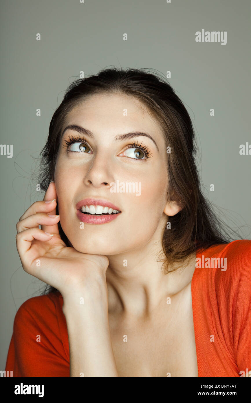 Young woman contemplatively looking away, portrait - Stock Image