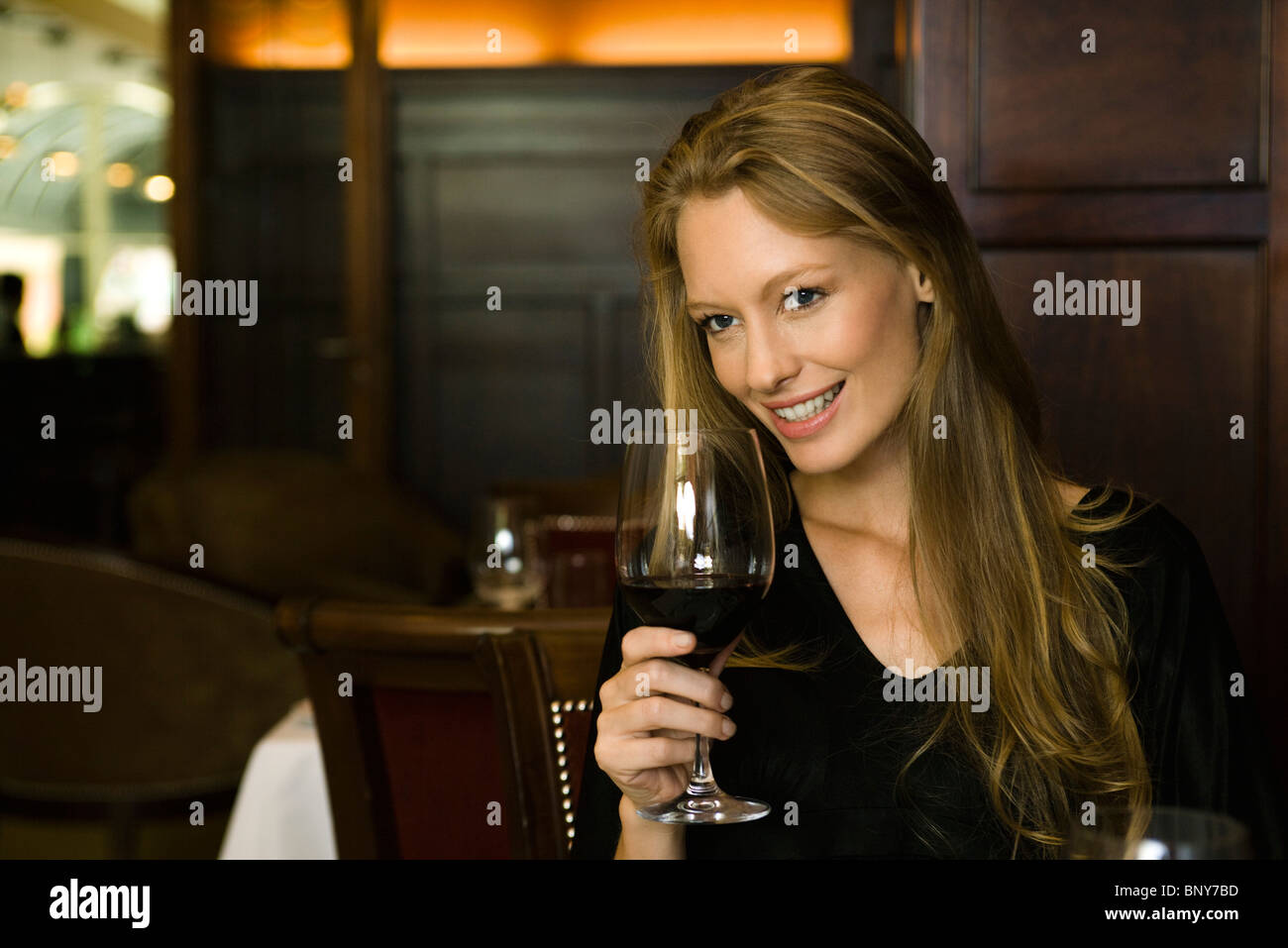 Woman enjoying glass of red wine in restaurant - Stock Image