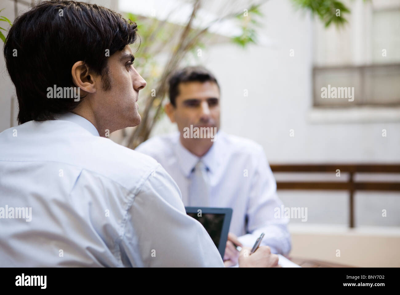 Businessman contemplatively looking away - Stock Image
