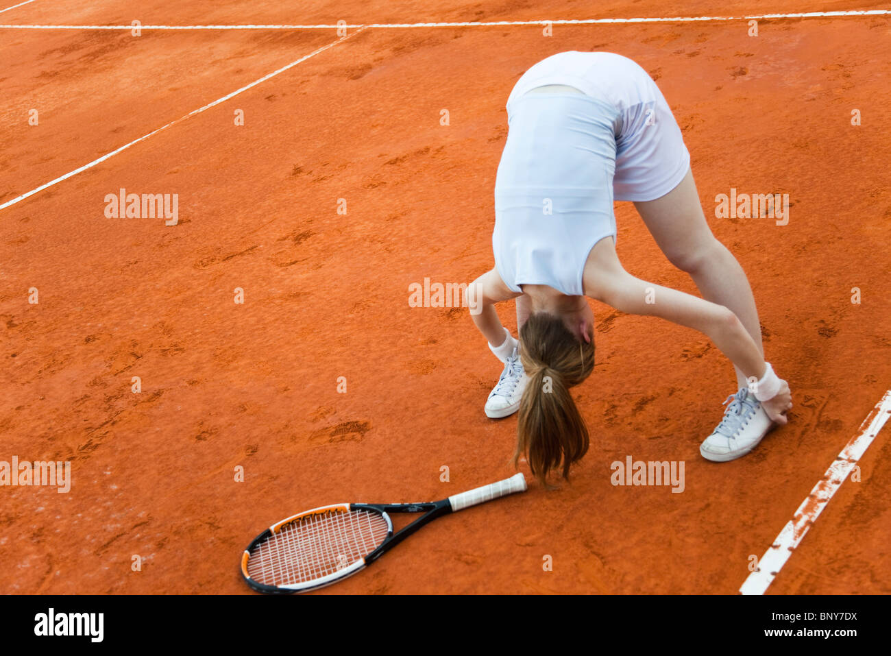 Tennis player stretching before game - Stock Image