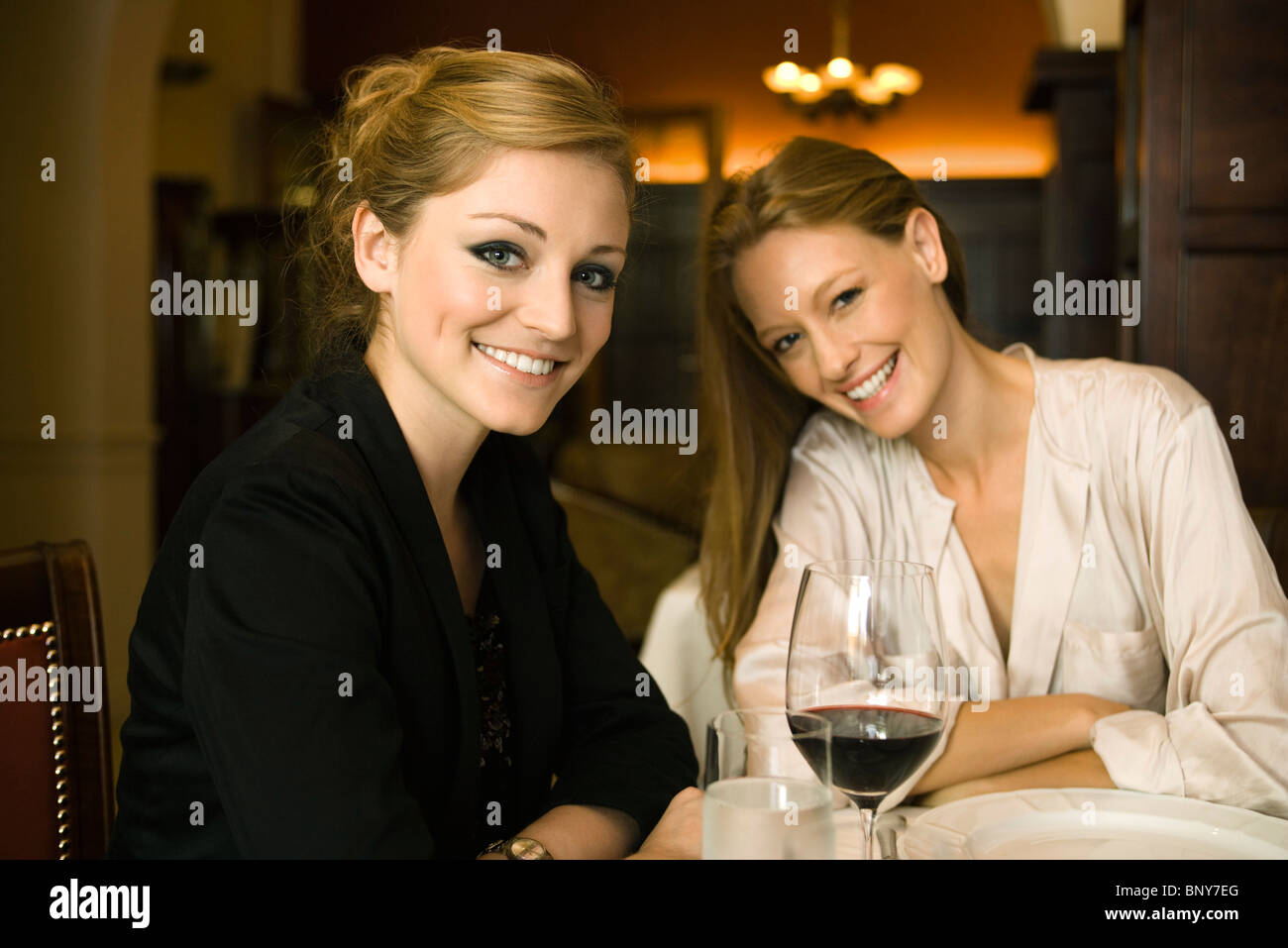Woman having glass of wine with friend in restaurant - Stock Image