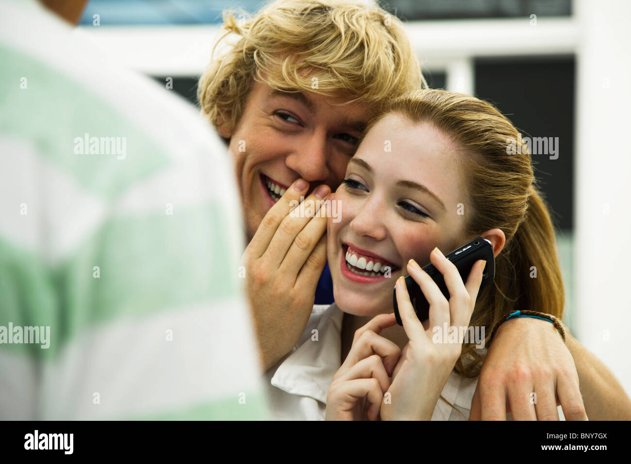 Young friends gossiping while one listens to cell phone - Stock Image