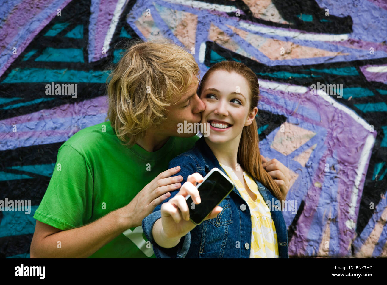 Young couple photographing themselves with cell phone, male kissing female's cheek - Stock Image