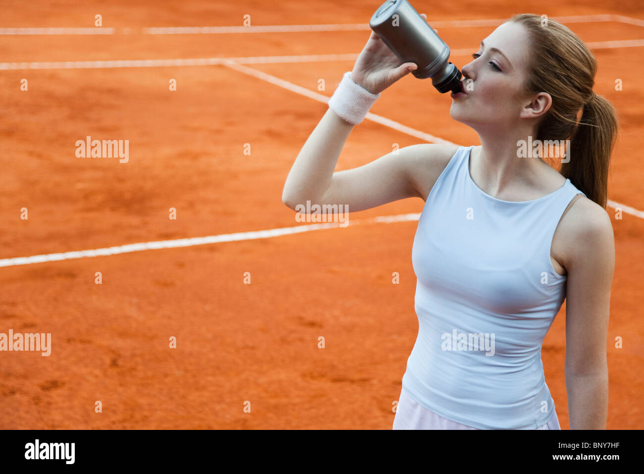 Tennis player drinking from water bottle - Stock Image