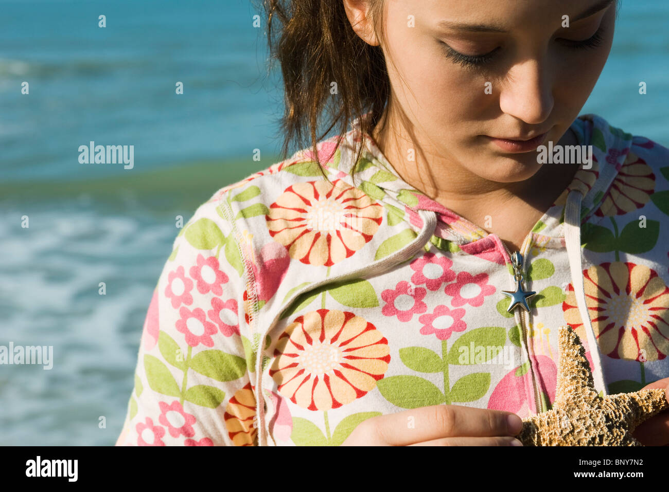 Teenage girl contemplating starfish Stock Photo